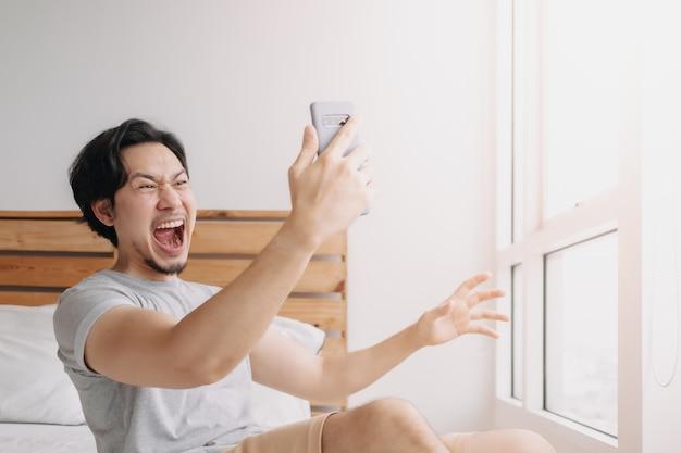 Шокированный и счастливый человек получает хорошие новости со смартфона