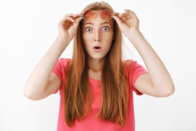 ショックを受けて感銘を受けた赤毛の女性。そばかすが飛び出して目を飛び出し、口を開けてあえぎながら、驚きとショックから眼鏡を脱いでいます。