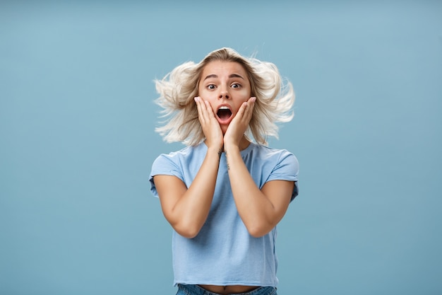 Шокированная и впечатленная молодая стильная европейка со светлыми волосами, держась за щеку от сочувствия и удивления, открыв рот лицом к ветру, позирует с прической, парящей в воздухе