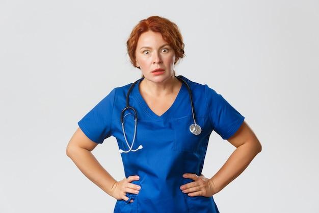ショックを受けて言葉を失った赤毛の女性看護師、スクラブの医者は腰に手を当てて信じられないような何かを聞きます。