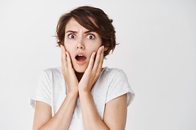 Шокированная и пораженная кавказская женщина, задыхаясь и хмурясь, смотрит на что-то ужасное, стоит на белой стене в повседневной футболке