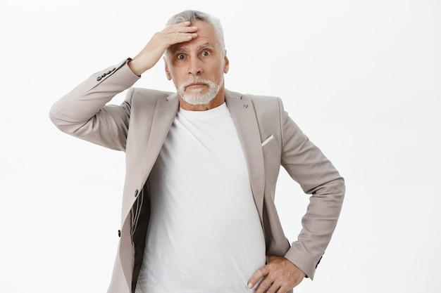 Шокированный и испуганный старший мужчина трогает голову и выглядит встревоженным