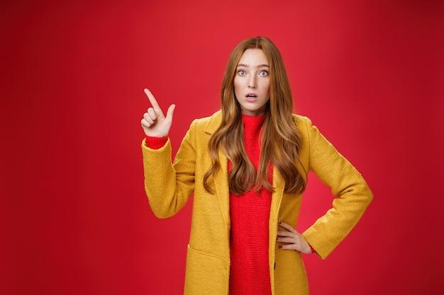黄色いコートを着たショックを受けて唖然としたかわいい、混乱した生姜の女の子は、心配し、驚いた口を開けて眉を持ち上げ、左上隅を指して、赤い背景にポーズをとっています。