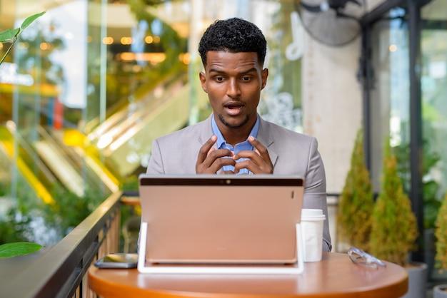 노트북 컴퓨터를 사용하는 커피 숍에서 충격과 놀란 아프리카 사업가