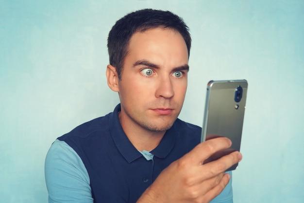 Шокирован и удивлен азиатский мужчина ищет смартфон. пораженный молодой парень читает сообщение по телефону.