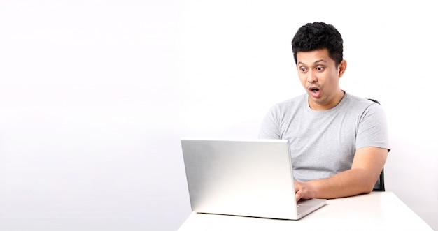 Потрясенный и удивленный азиатский человек который имеет страницу компьютера. с копией пространства.
