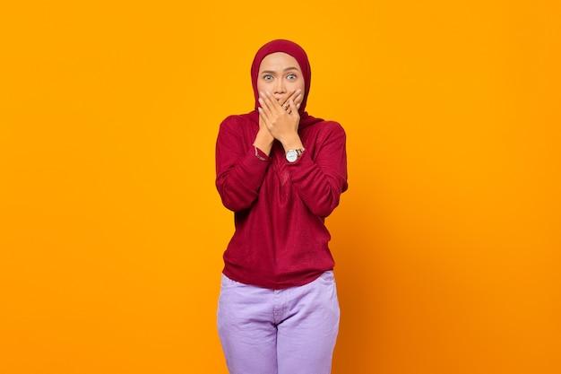 黄色の背景の上に手で口を覆うショックと驚きのアジアの女性
