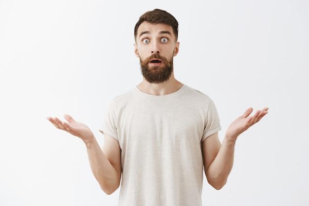 Шокированный и удивленный бородатый парень выглядит удивленным