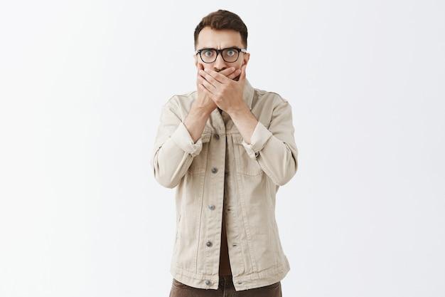 Шокированный и удивленный бородатый мужчина в очках позирует на белой стене