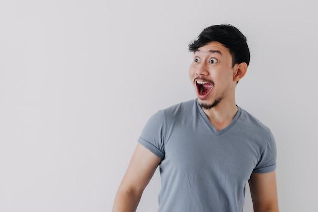 白い背景で隔離の青いtシャツの男のショックと驚きの顔