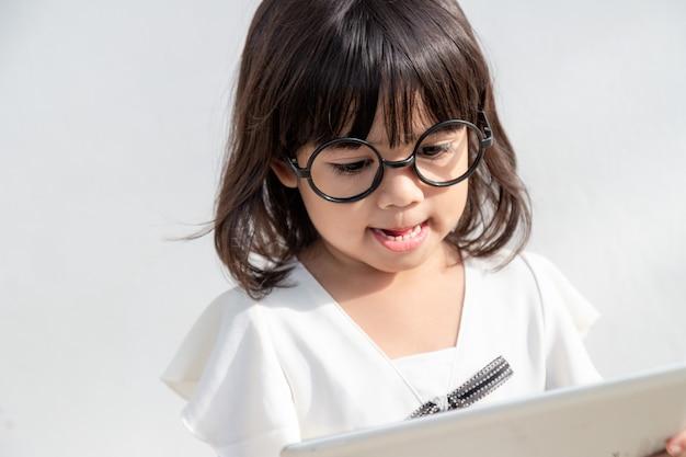 驚きのためのデジタルタブレットコンピューターの概念を持つインターネット上のショックを受けて驚いた少女