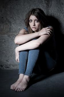 충격과 공포. 어두운 방에서 바닥에 앉아 있는 동안 카메라를 보고 충격을 받은 젊은 여성