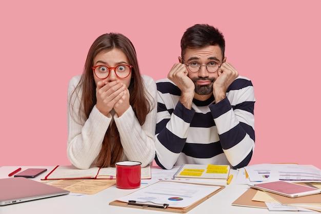 ショックを受けて疲れた女性、男性は多くの紙の仕事に不満を感じ、一緒にデスクトップに座って、最新の電子機器を使用します
