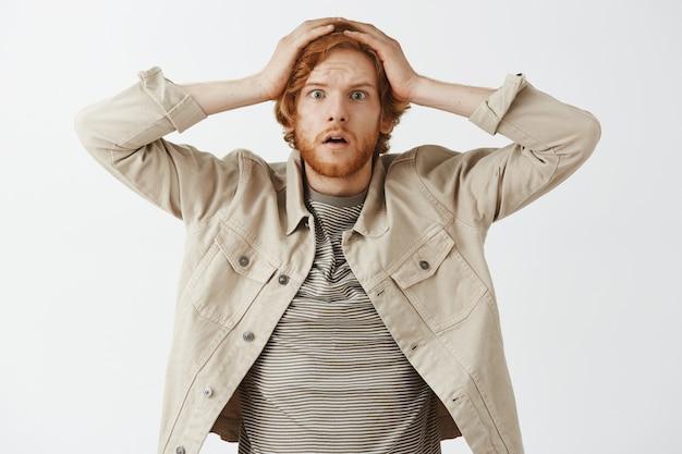白い壁に向かってポーズをとってショックを受けて心配しているひげを生やした赤毛の男