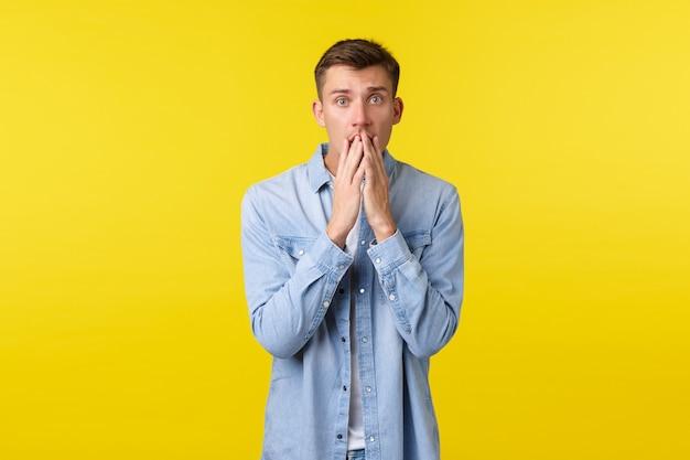 カメラを心配して見て、唇に触れて、カメラを心配して見つめているショックを受けて心配している金髪の男は、ひどい事故について聞いて、思いやりと共感を表現し、黄色の背景。
