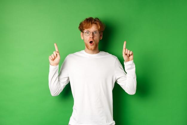 헐떡 거리고 카메라를 쳐다보고, 광고에서 손가락을 가리키고, 녹색 배경 위에 서있는 안경에 충격과 걱정 빨간 머리 남자.