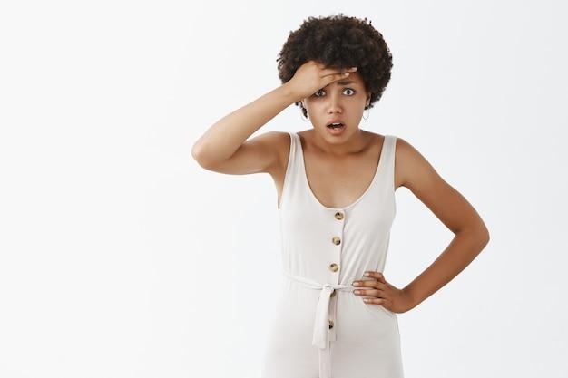 흰 벽에 포즈를 취하는 충격과 걱정 세련된 소녀