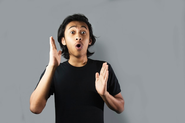 검은 티셔츠에 수염을 기른 잘생긴 아시아 남자의 충격과 와우 얼굴