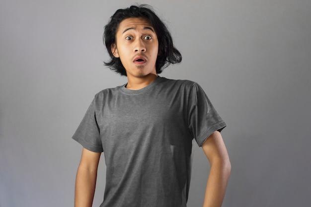 회색 티셔츠에 수염을 기른 잘생긴 아시아 남자의 충격과 와우 얼굴
