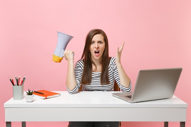 Shocked angry woman screaming spreading hands holding megaphone sit and work at white desk at office with pc laptop isolated on pastel pink background. achievement business career concept. copy space.
