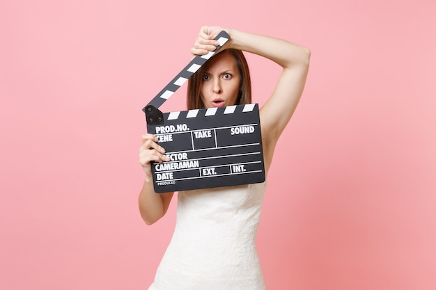 Shocked angry woman in white dress covering face with classic black film making clapperboard