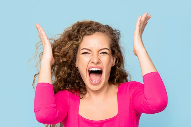 Shocked angry young caucasian woman shouting isolated on light blue wall
