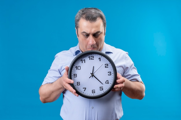 Shocked ans surprised middle age man in blue striped shirt holding wall clock with hands on a blue background