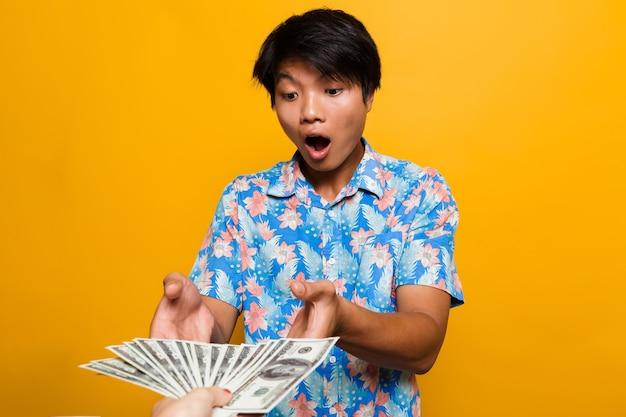 Shocked asian man receiving money banknotes