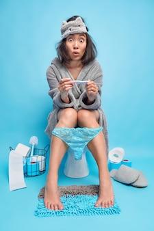 Шокированная азиатская женщина узнает о беременности, получает положительный результат утром, сидит на унитазе, носит маску для сна, а халат держит ноги на ковре, позирует в туалете у синей стены
