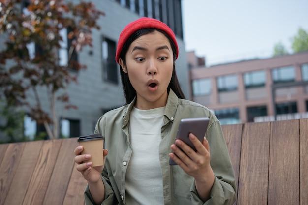 オンラインショッピングのために携帯電話を使用してコーヒーカップを保持しているショックを受けたアジアの女性