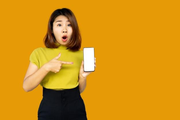 驚きの顔でスマートフォンを指してショックを受けたアジアの女性
