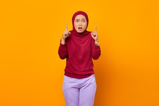 両方の人差し指を上げるショックを受けたアジアの女性の肖像画