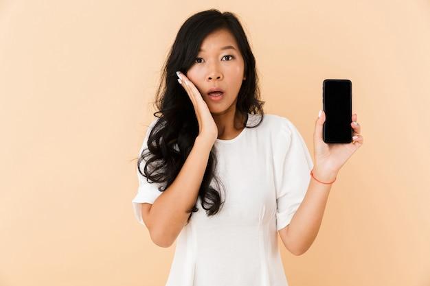 電話のディスプレイを示すベージュの壁のスペースに孤立してポーズをとってショックを受けたアジアの女性。