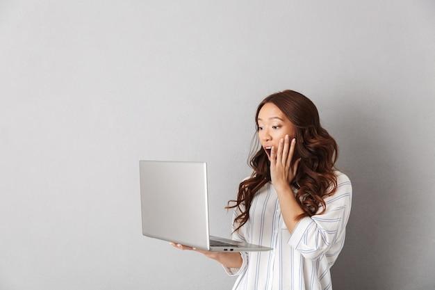 Шокированная азиатская женщина, стоящая изолированно, глядя на портативный компьютер