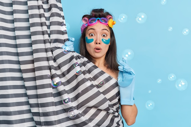 Shocked asian woman surprised as someone came in bathroom while she was taking shower hides her naked body undergoes beauty treatments makes hairstyle poses indoor soap bubbles around. hygiene concept