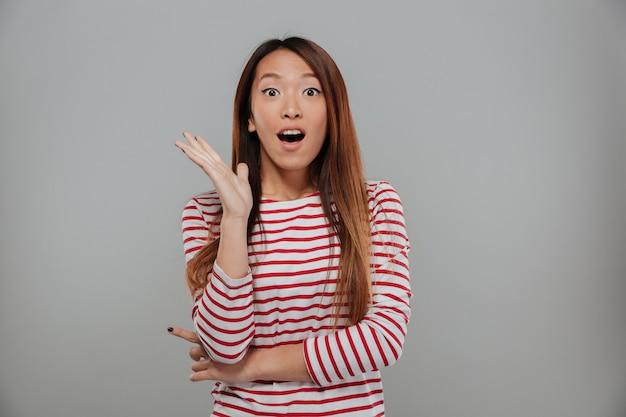 Donna asiatica colpita in maglione che esamina la macchina fotografica con la bocca aperta sopra fondo grigio