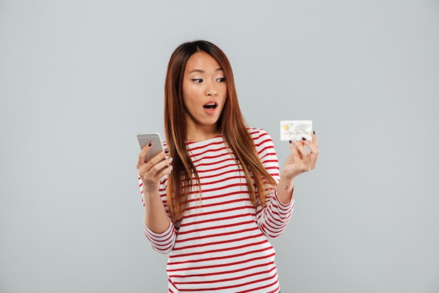 Shocked asian woman in sweater using smartphone and credit card over gray background