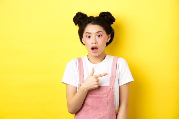 매력적인 메이크업, 입을 열고 로고를 오른쪽으로 가리키고 광고를 표시하고 노란색에 서서 충격을받은 아시아 여성.