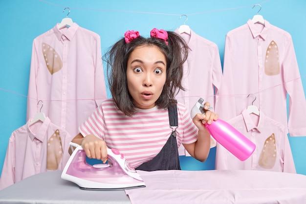 2つのポニーの尾を持つショックを受けたアジアの女性は自宅で洗濯物をアイロンをかけるのに忙しい洗剤ボトルを保持します