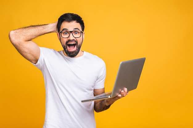 Shocked astonished amazed bearded man in eyeglasses looking at laptop screen isolated over yellow background.