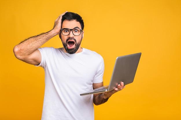 Шокирован, изумлен изумлен бородатый мужчина в очках, глядя на экран ноутбука, изолированные на желтом фоне.