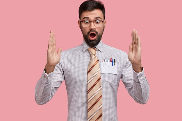 Shocked astonished bearded man gestures actively, shows something very huge, has surprised expression, wears formal shirt with tie
