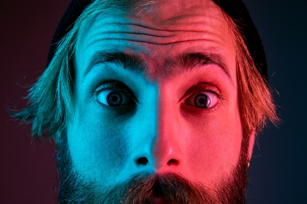 Shocked, astonished, close up. caucasian man's portrait on gradient studio background in neon light. beautiful male model with hipster style. concept of human emotions, facial expression, sales, ad.