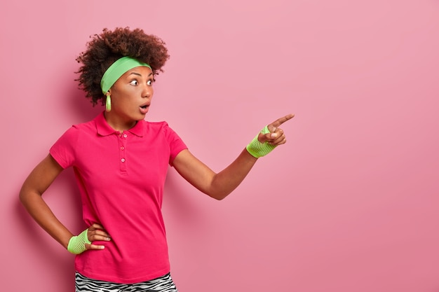놀란 곱슬 머리의 젊은 여성이 눈을 도청하고 손가락을 멀리 가리키며 놀라운 것을보고 입을 벌리고 스포츠 옷을 입은 모습