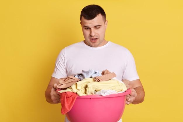 洗濯用の汚れた衣類でいっぱいの洗面器を持っているショックを受けた驚いた男