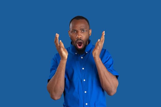 ショックを受け、驚いた。青い壁に隔離された若いアフリカ系アメリカ人男性のモノクロの肖像画。美しい男性モデル。人間の感情、顔の表情、販売、広告のコンセプト。若者文化。