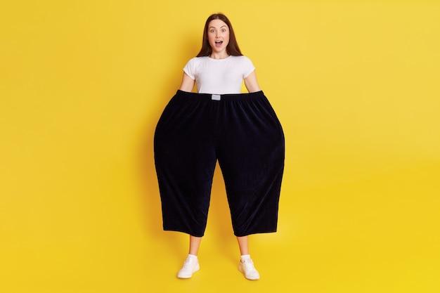 Шокированная изумленная женщина в старых слишком больших черных штанах держит руки в штанах. смотрит в камеру с открытым ртом и большими глазами, удивляется выражению лица, позирует изолированно над желтой стеной.