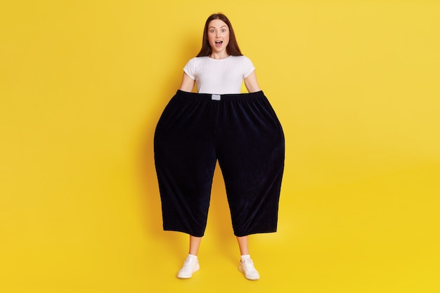 Shocked astonished woman wearing old too big black trousers keeps hands in pants. looks at camera with open mouth and big eyes, has surprised facial expression, posing isolated over yellow wall.