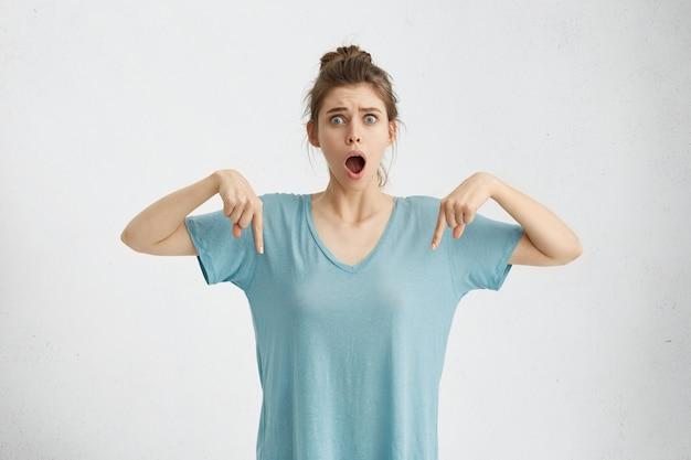 Шокированная изумленная молодая кавказская женщина с пучком волос, глядя с ртом, упала, указывая пальцами вниз