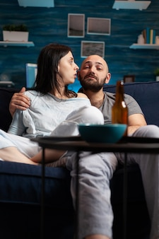 Shocked astonished young couple looking at documentary show at tv